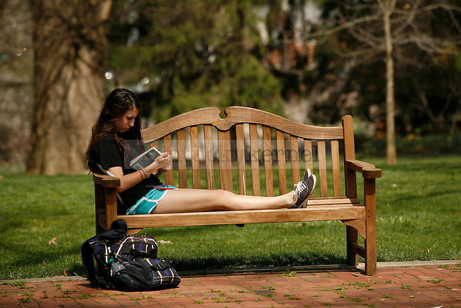 Psychology freshman Nikki Stasuck reads a book on a bench behind Maxwell place in Lexington, Ky., on Wednesday, April 10, 2013. Photo by Tessa Lighty | Staff