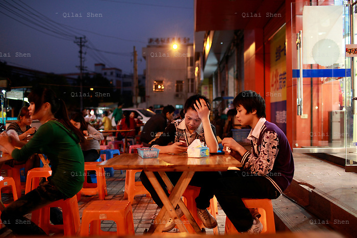 "Two young workers just off their shifts at a shoe factory in a area known as ""Xie Du"", or shoe capital, check their cellphones while waiting for their dinner in the city of Wenzhou, Zhejiang Province, China on 23 October, 2011. Wenzhou has seen a spate of business owners disappearing under the pressure of debt, as small and medium size businesses face increasing difficulties in securing loans, while the slow recovery of the European and U.S. economies continues to disappoint exporters."