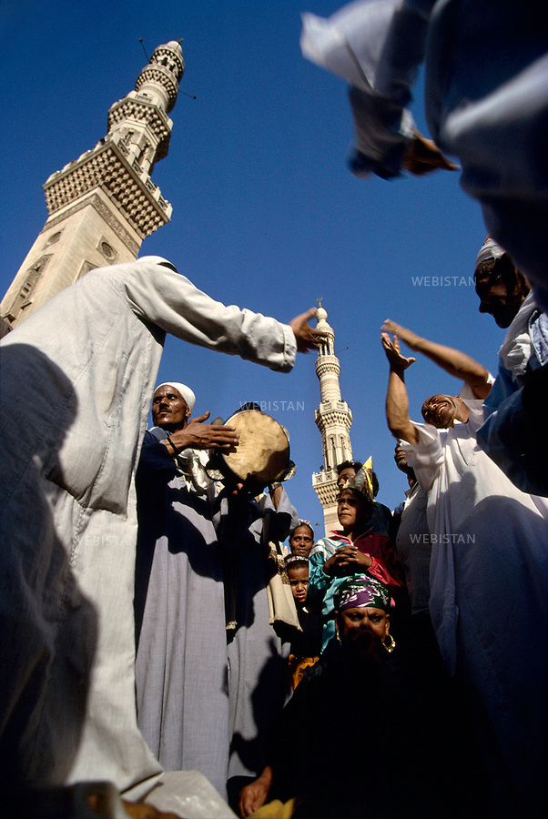 "Egypt. Near Tanta. May 1996. The three days of festival (""mouled"") for Sidi Ahmad el-Badaoui, greatest Muslim saint of the country start. Musique and tambourin, songs and danses at the feet of Tanta's mosque accompany the faithful's trances..Egypte. Pres de Tanta. Mai 1996. Les trois jours de fete (""mouled"") en l'honneur de Sidi Ahmad el-Badaoui, plus grand saint musulman du pays commencent. Musique et tambourins, chants et danses au pied de la mosquee actuelle de Tanta accompagnent les transes des fideles."