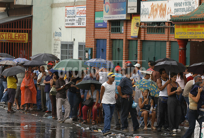 Venezolanos   esperan  en la fila para emitir su voto  en Caracas. Desde la mañana temprano una multitud de venezolanos se acercaron a los centros de votación para decidir en un referendo si el presidente Hugo Chavez continúa o no en su cargo.+ politica, eleccion *Venezuelans wait in line under a heavy rain to cast their votes. Venezuelans crowded from early morning the polling stations to decide in a referendum wheter or not President Hugo Chavez will remain in charge *Des Vénézueliens attendent en file indienne pour voter dans un bureau de vote dans le quartier de Brisas de Propatria à Caracas. Depuis tôt le matin, une multitude de Vénézueliens se sont dirigés vers les bureaux de vote afin de se prononcer sur le maintien d'Hugo Chavez à la tête de l'Etat. +élections, électeurs, politique......Venezuelans wait in line to cast their votes in the Caracas  suburb of Brisas de Propatria, Sunday, August 15th, 2004. Venezuelans crowded from early morning the polling stations to decide in a referendum wheter or not President Hugo Chavez will remain in charge/