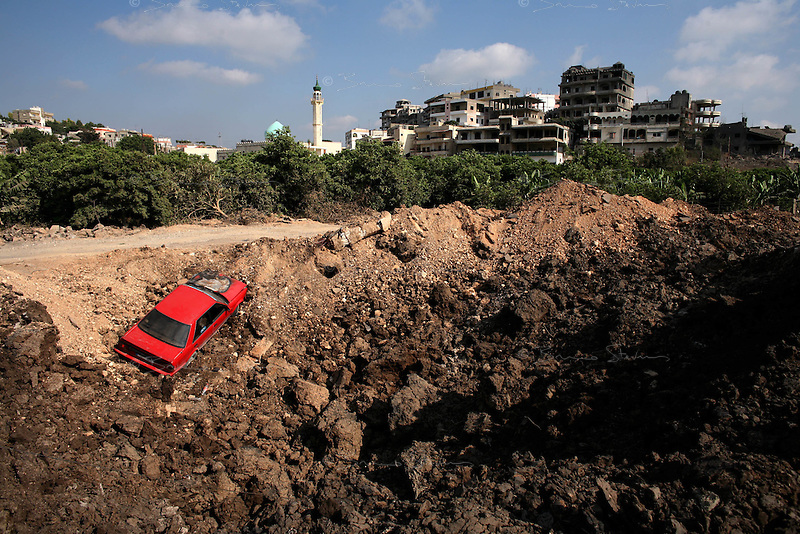 near Tyr, Lebanon, Aug 4 2006.A civilian car lies in a very large crater left by an Israeli bomb on the coastal road just north of Tyr..