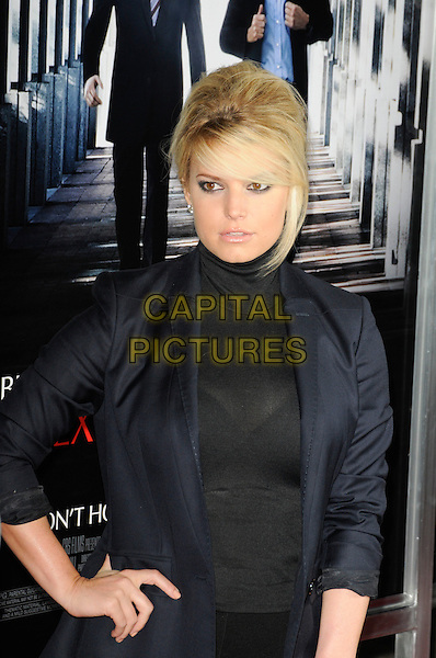 """JESSICA SIMPSON.arriving at the premiere of """"Extraordinary Measures"""" at Grauman's Chinese Theatre in Hollywood, California, USA,   January 19th, 2010..arrivals half length hand on hip hair up fringe beehive make-up black blazer jacket polo neck top  sheer see top thru  through  bra navy blue .CAP/ROT.©Lee Roth/Capital Pictures"""