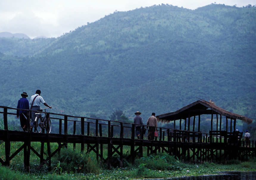 Burmese with bicycles walk down a bridge at Inle Lake, Shan State, Burma, 2006.