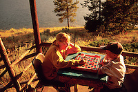 Two children sit on a porch near a lake playing a game of checkers.