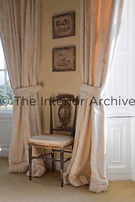 An antique chair flanked by elegantly draped curtains in the master bedroom