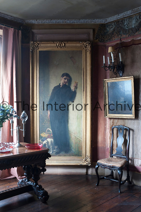 A wistful Victorian portrait hangs against faded crimson wall hangings in a living room