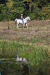 A young cowgirl riding her horse next to a pond