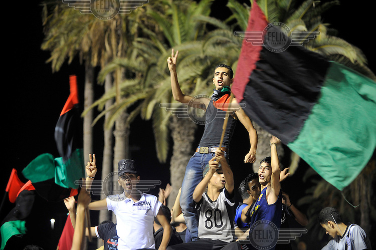 Young men sing and wave a flag as they celebrate at Martyrs' Square in Tripoli. After a six month revolution, rebel forces finally managed to break into Tripoli and have taken control of Bab al-Aziziyah, Col Gaddafi's compound and residence. Few remain that are loyal to Gaddafi in the city; it is seeming that the 42 year regime has come to an end. Gaddafi is currently on the run.