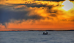 Fishermen check a net under the ice of Great Slave Lake. Wild sky.