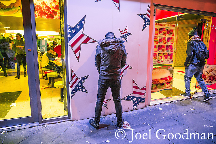 © Joel Goodman - 07973 332324 . 01/01/2016 . Manchester , UK . A man urinates up against a fast food takeaway wall . Revellers in Manchester on a New Year night out at the clubs around the city centre's Printworks venue . Photo credit : Joel Goodman