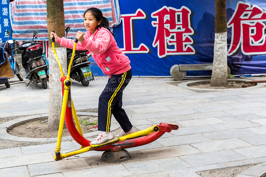 Guilin, China.  Young Girl Exercising on Sidewalk Public Exercise Machine.