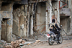 A man with a weapon rides past damaged buildings in the old city of Mosul, Iraq. This portion of the city was heavily damaged in 2016 and 2017 when Iraqi forces, supported by U.S. air strikes, combated Islamic State fighters who held residents of the old city as human shields.