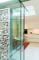 A wall of river pebbles encased in a glass panel in the kitchen/dining area