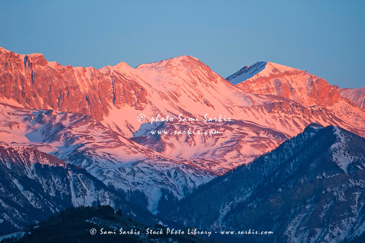 Snowy mountain range with a rosy hue at sunset.