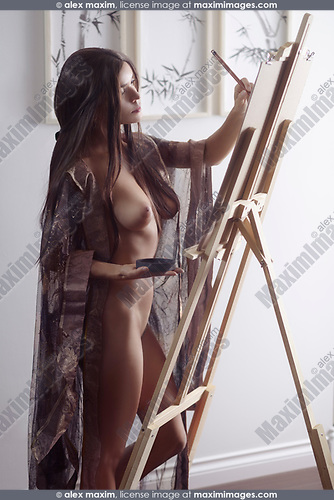 Beautiful young woman sumi-e artist with an easel painting naked in her home studio