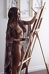 Beautiful young woman sumi-e artist with an easel painting naked in her home studio Image © MaximImages, License at https://www.maximimages.com
