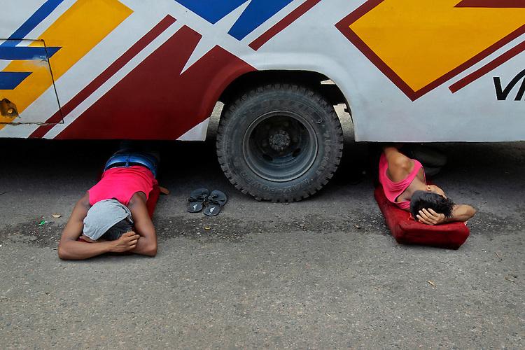 Bangladeshi men sleep under a bus on a road in Dhaka, Bangladesh.