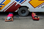 Bangladeshi men sleep under a bus on a road in Dhaka, Bangladesh.
