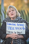 Rebecca Dare holds a sign and sings outside the fence surrounding the Federal Detention Center in Seatac, Washington, during a June 24 prayer vigil in support of immigrant parents inside the prison who've been separated from their children. The vigil was sponsored by the United Methodist Church.