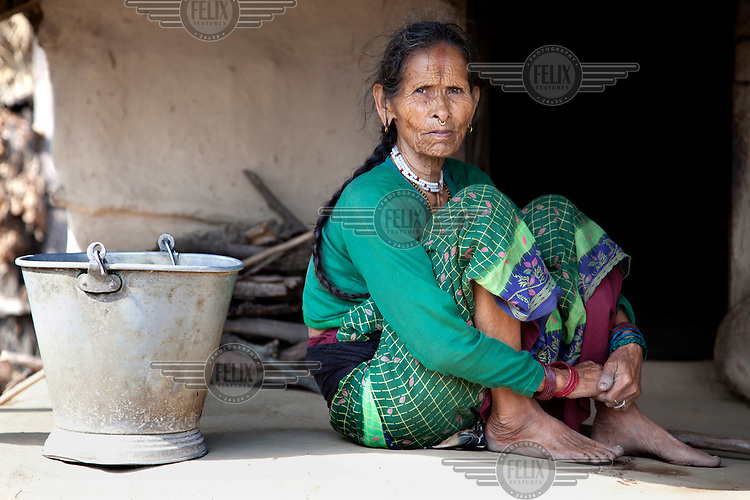 An elderly woman sitting in front of her house.