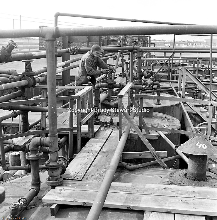 Lawrenceville PA: Location photography at the Atlantic Refining site at 5733 Butler Street. View of workman adjusting valves on top of one of the storage tanks.<br /> This track of land has been involved in oil-related refining for over 100 years.  ARCO sold the property to SUNOCO which still operates a storage facility at 5733 Butler Street.