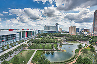 This is another over view from above of the Discovery Green Park in downtown Houston Texas.  The Discovery Green Park is a 12 acreas park in the heart of downtown Houston near the convention center, the Toyota Center, and Minute Maid Park.  From this vantage point you can see the park plus the George Brown Convention Center with it new Avenida Plaza along with  some of the high rise condos and hotels in the area. You  can also catch a glimps of the Wings Over Water sculpture at the other end of the plaza.  You can see Kinder Lake in the park with people out on the water in their kayaks along with the children cooling off in the spray water fountain plus many other areas of the park not to mention the people out just enjoying their time there. This park located in downtown Houston has over 600 free events every year from music, movies, yoga, to name a few.