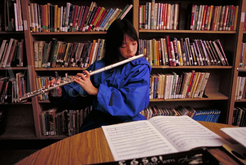 ELEMENTARY SCHOOL BAND PRACTICE - GIRL PLAYING FLUTE. ELEMENTARY SCHOOL STUDENTS. OAKLAND CALIFORNIA USA CARL MUNCK ELEMENTARY SCHOOL.