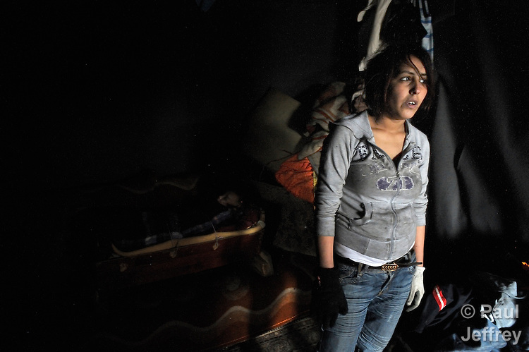 Skurta Hodici, 17, looks out the door of her home in an illegal Roma settlement in Belgrade, Serbia, in February 2012. Her daugther Deljana, 11 months old, sleeps behind her. The families that lived here, most of whom survive from recycling cardboard and other materials, were forcibly evicted in April 2012. Many including Hodici were moved into metal shipping containers on the edge of Belgrade.