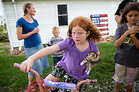 "Emily Rouse, left, wife of Jason Rouse and their children Willie Rouse, 6, back left, Elizabeth Rouse, 8, center, and Lydia Rouse, 9, right, chat outside their home on Monday, July 27, 2015 in Cumberland, Iowa. Rouse is in his second year of using Farmobile to collect data and information on his farm. ""Once you get an idea of what you got you're able to change things and Farmobile allows us access to that anytime,"" he said. Rouse said it allows him to fine tune or make decisions on what he needs to change or improvise. ""It paints a picture of the whole field as you're overlooking it,"" he said."