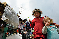 Little Colombian girls pose for a picture in the 'Invasión', a temporary slum in Bogota, Colombia, 1 April 2006. The internal armed conflict in Colombia together with lack of social network caused appearence of small invasion slums in all Colombian urban zones in last years. These illegal settlements rise quickly in free uncontrolled spaces between industrial buildings, both in the city centres and peripheries. Shacks do not have sanitation network, neither electricity. Most of their inhabitants are war fugitives violently displaced from their original lands in the country by guerrilla or paramilitary forces. Picking up the rubbish and recycling it is a common survive strategy for people living in these temporal ghettos until those are not dismantled by city administration.