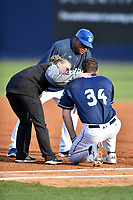 Asheville Tourists athletic trainer Kelsey Branstetter and manager Robinson Cancel look over Grant Lavigne (34) after he was hit by a pickoff attempt during a game against the Augusta GreenJackets at McCormick Field on April 6, 2019 in Asheville, North Carolina. The Tourists defeated the GreenJackets 6-3. (Tony Farlow/Four Seam Images)