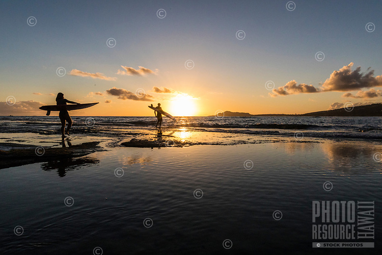 A couple heading out for an evening surf session are reflected in tide pools near Koko Head, East O'ahu.