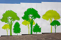 Demolition site walls decorated with tree graphics around the site of the old National Stadium in  Gaiemmae, Tokyo, Japan. Friday May1st 2015. The stadium is being demolition to make way for the controversial 2020 Olympic Stadium designed by British architect, Zaha Hadid.