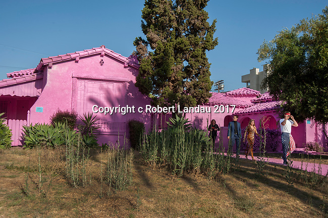 "People looking at neighborhood houses painted bright pink as part of an art project in Los Angeles, CA. Impermanent Art curated this temporary installation for a  project called ""iMpermanence."" It's the first of many that will transform properties that are scheduled to be demolished and developed. @themostfamousartist and @themuralagency painted four houses completely in pink ""as a way of starting a dialogue about the intersection of development, community, public art and social media."