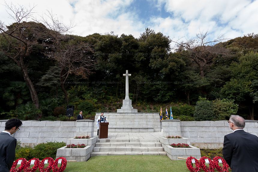 Reverend  Dr. Simon C Ro gives a Christian service at the Cross of Sacrifice with wreaths of poppies during the Remembrance Sunday ceremony at the Hodogaya, Commonwealth War Graves Cemetery in Hodogaya, Yokohama, Kanagawa, Japan. Sunday November 11th 2018. The Hodagaya Cemetery holds the remains of more than 1500 servicemen and women, from the Commonwealth but also from Holland and the United States, who died as prisoners of war or during the Allied occupation of Japan. Each year officials from the British and Commonwealth embassies, the British Legion and the British Chamber of Commerce honour the dead at a ceremony in this beautiful cemetery. The year 2018 marks the centenary of the end of the First World War in 1918.