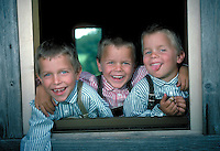 Three young boys in striped shirts and overalls, smiling and goofing around, while hanging out of window.