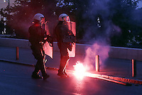 Pictured: A flare lands at the feet of riot police officers  Sunday 09 May 2016<br /> Re: Riots break out between protesters and police in Syntagma Square, while MPs in the Greek Parliament vote for new tax, pension and welfare reforms in Athens, Greece