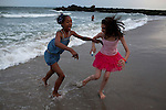 Emani White, 12, left, and Melissa Young, 11, right, play in the sea at dusk at Rockaway beach in New York on June 24, 2012.