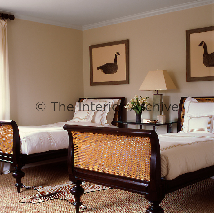 The guest bedroom is furnished with mahogany and cane twin beds and perpetuates the natural decorating style throughout the house