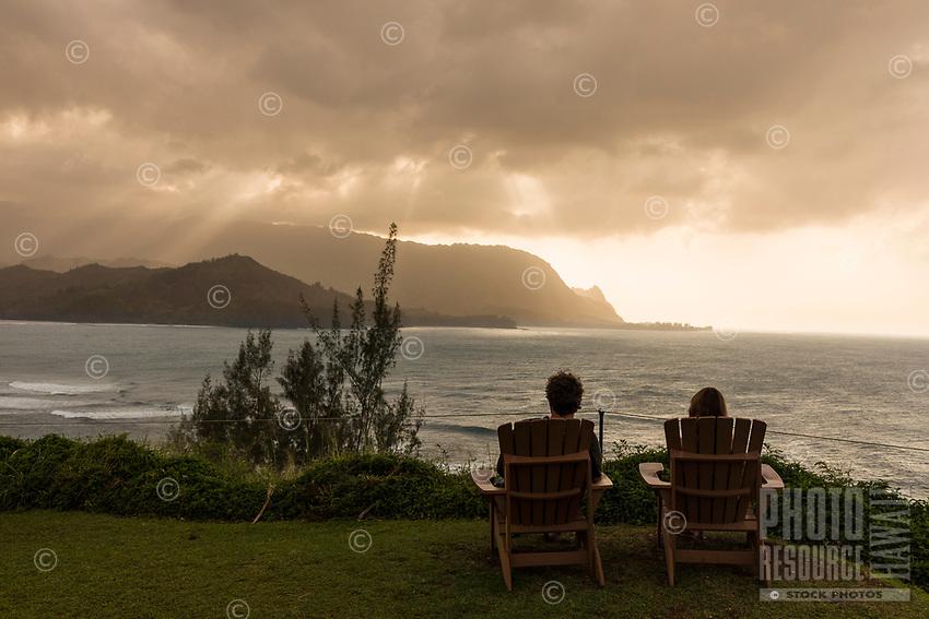 A couple watches the sun set over Mount Makana (nicknamed Bali Hai) and rest of the mountain range, Princeville, Kaua'i.