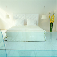 During the daytime the bed is dressed with white patent-leather cushions to compliment the white leather headboard