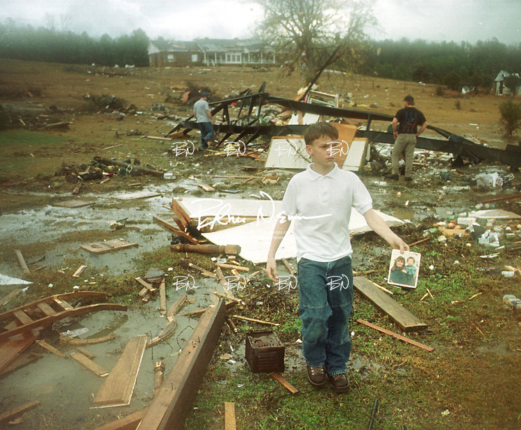 Chad Malone gathers a family photo from the ground surrounding the mobile home he lived in that was destroyed by a tornado at Hawkins Crossing in Yalobusha County, Miss. Monday, January 3, 2000. The floor from the mobile home was found about 200 yards from its original location.