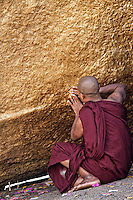 A monk applying gold leaf to the Golden Rock, Myanmar