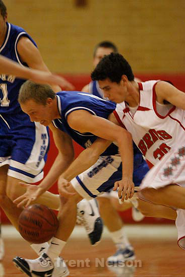Bingham's Nate Girsberger (4, left) drives with Bountiful's Dillon Salazar (30) reaching in for the steal. Bountiful vs. Bingham high school boys basketball, Friday, December 4 2009 in Bountiful.
