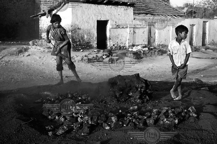 Two boys prepare a fire where coke and charcoal are made from coal scavenged from an open cast mine. On the margins of such mines small communities of people make a precarious living scavenging coal and selling charcoal and coke they make from it. Below ground permanent fires burn, fuelled by seams of coal. The ground can be too hot to walk on and there is an ever present danger that houses will collapse into the vast underground caverns that are left unfilled after mining operations have ended.