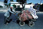 An unidentified man pushing a cart with his belongings and his wife on July 22, 1996 in Kabul, Afghanistan. The Taliban took over most of Afghanistan in 1996, and have forced the people to live under strict muslim law. Girls are not allowed to attend schools and women are not allowed to work. .(Photo: Per-Anders Pettersson/Liaison Agency)