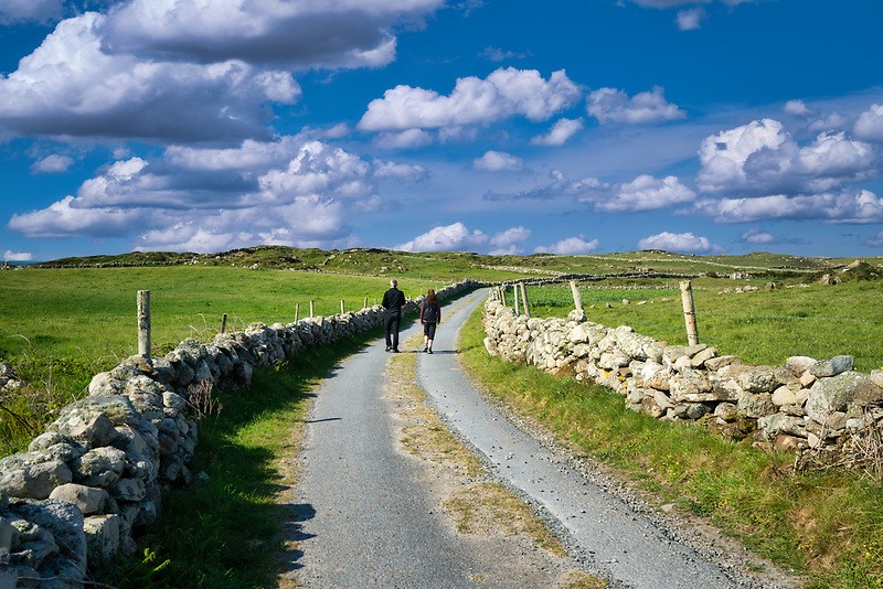couple walking on road on Omey Island. Connemara,County Galway,Ireland
