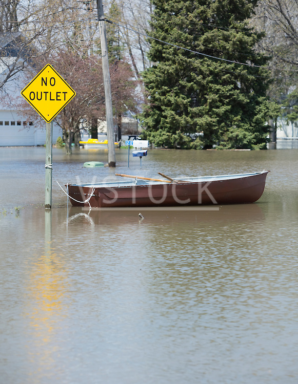 Rowboat moored to road sign drifting on flooded street