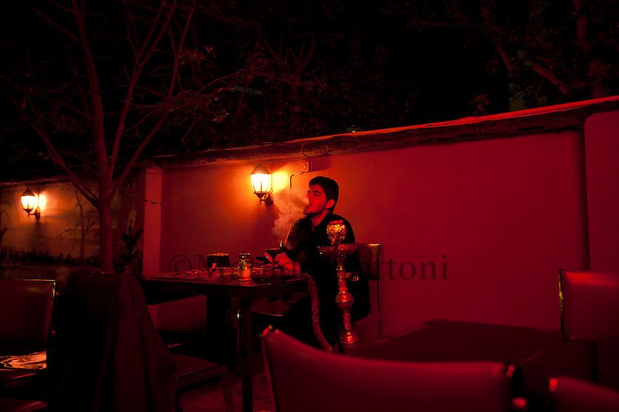 Iraq - Kurdistan - Sulaymaniyah -   Youg man smoking shisha  at night in a cafe'
