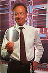 Andrew Grove, CEO of Intel Corporation, holds an Intel 1386 microprocessor at the company plant in Santa Clara, California. The wafer serves as the brains of a personal computer and is worth about $200. It is the most popular product made by Intel. (AP Photo/Paul Sakuma)